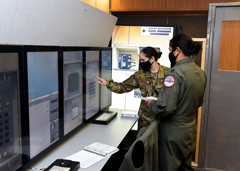 From left, Capt. Grazia Castagna, 625th Strategic Operations Squadron intelligence officer, and Capt. Stephanie Konvalin, 625th STOS strike planner, conduct operations in a newly-established trainer March 5, 2021, at Offutt Air Force Base, Neb.