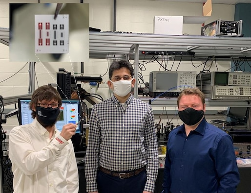 From the left to right, Drs. Derek A. Bas, Piyush J. Shah and Michael R. Page. In the tweezers, Bas is holding a chip that contains an array of four isolators. A state-of the-art commercial RF isolator has a much greater size and weight than the AFRL device. (U.S. Air Force photo/Dr. Michael Wolf)