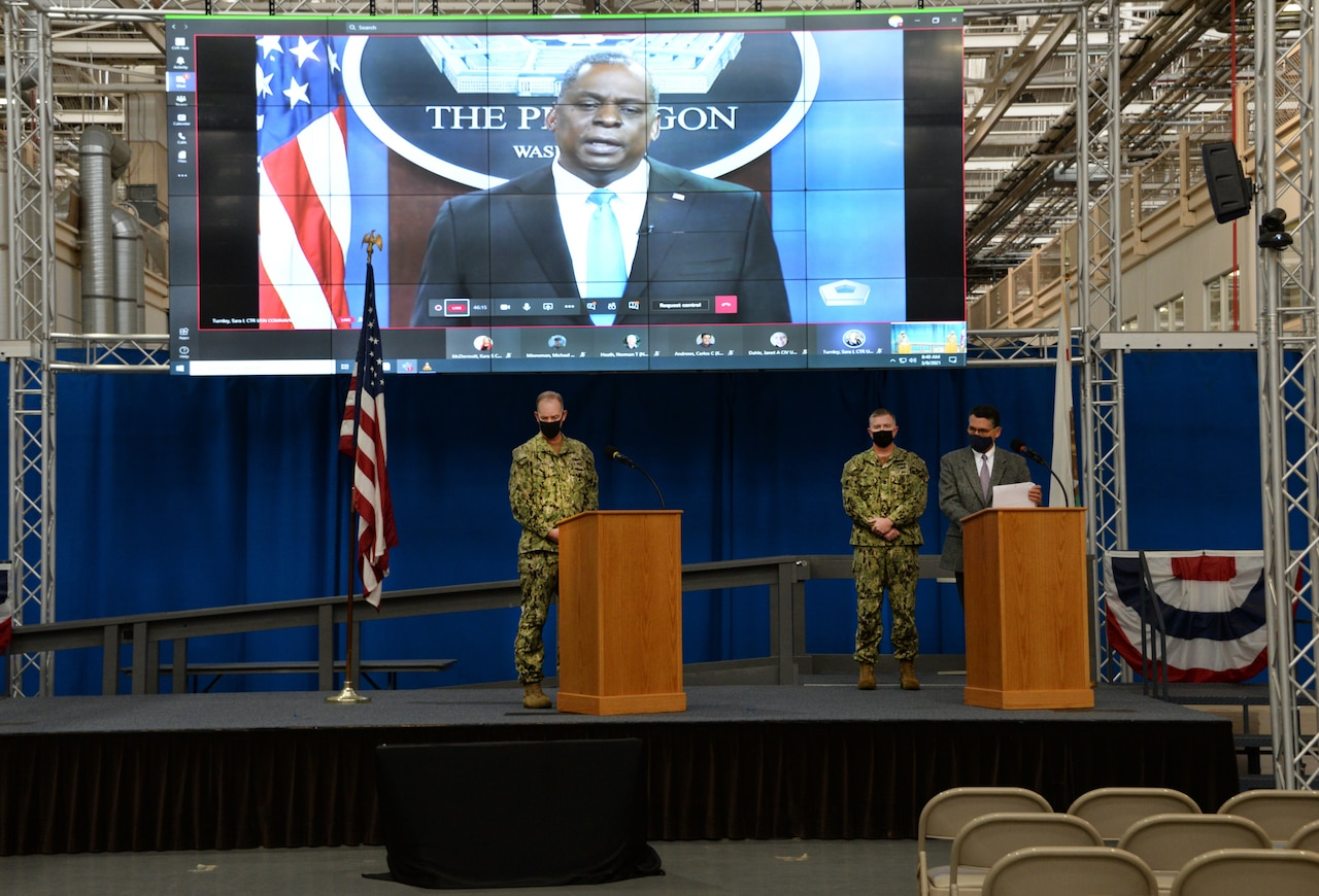 Two military personnel and a man in civilian clothes stand behind lecterns on a stage. In the rear, a large display screen shows a video that features the secretary of defense speaking from the Pentagon..