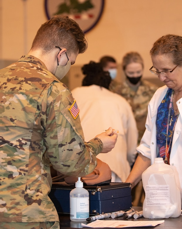 Alabama Department of Public Health officials observe Alabama National Guard Mobile Vaccination Team members demonstrating vaccination technique to ensure compliance with state and federal standards March 16, 2021, in Montgomery, Ala. The teams will be administering COVID-19 vaccines to members of rural Alabama communities starting March 23.