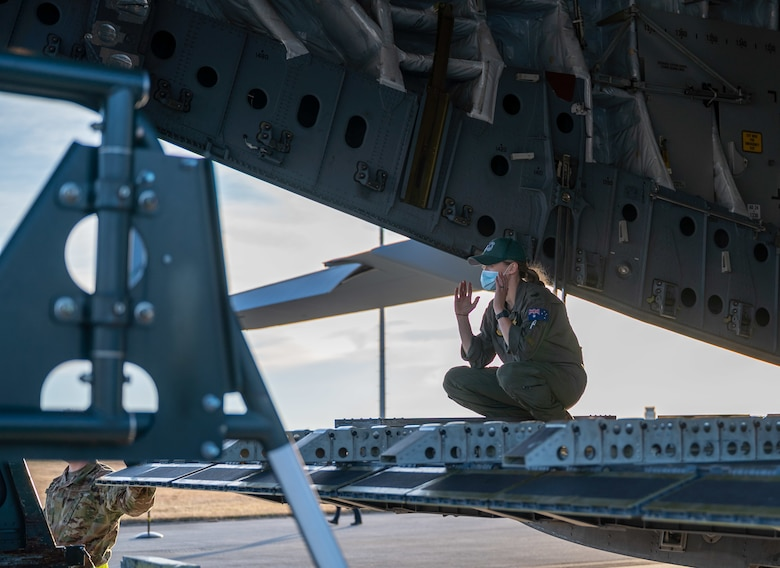 Sgt. Madison Cave-Freeman, Royal Australian Air Force 36th Squadron loadmaster, marshals a K-loader to the ramp of a RAAF C-17 Globemaster III at Dover Air Force Base, Delaware, March 13, 2021. The U.S. and Australia maintain a robust relationship underpinned by shared democratic values, common interests and cultural bonds. The U.S.-Australia alliance is an anchor for peace and stability in the Indo-Pacific region and around the world. (U.S. Air Force photo by Airman 1st Class Faith Schaefer)