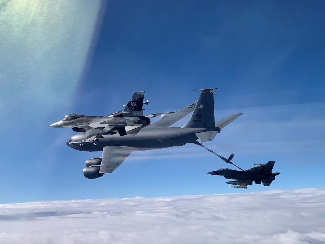 An F-16 Fighting Falcon from the 18th Aggressor Squadron receives fuel from a KC-135 Stratotanker from the 203rd Air Refueling Squadron March 10, 2021, near Oahu, Hawaii. The aircraft practiced combat tactics alongside fifth-generation F-22 Raptors from the 199th and 19th Fighter Squadrons for exercise Pacific Raptor. The Alaska-based F-16s, known as 'Aggressors,' simulate combat tactics likely to be faced in the event of an air-to-air battle.