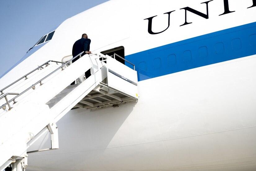 Man in business attire boards plane.
