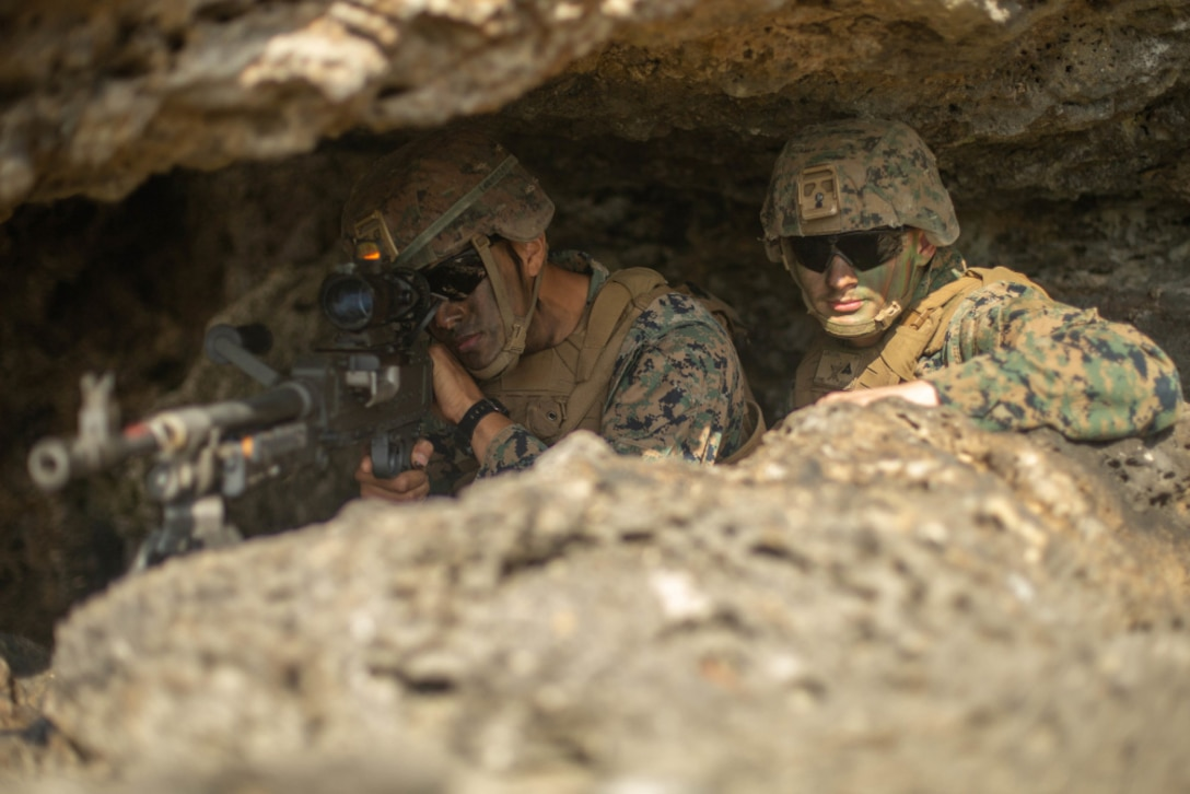 One Marine aims his gun as a second Marine sits next to him under a large rock.