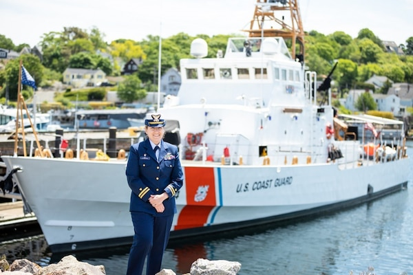 Lt. Tara Pray stands in front of U.S. Coast Guard Cutter Key Largo homeported in historic Gloucester, Massachusetts. (U.S. Coast Guard Photo)