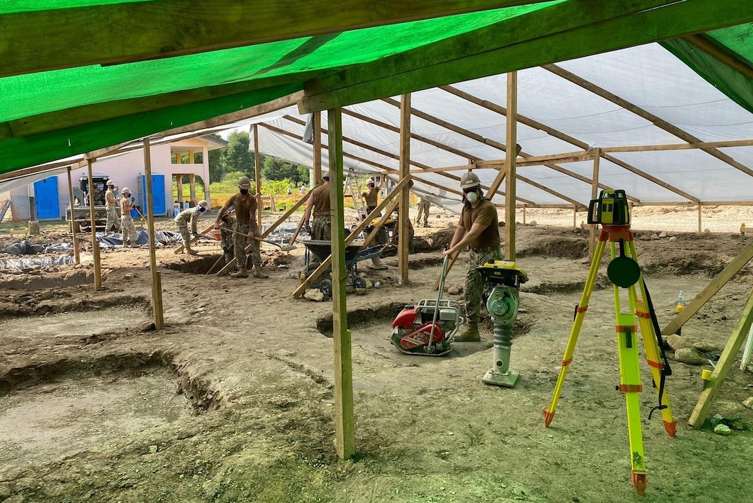 A group of men use construction equipment under a large green tarp.