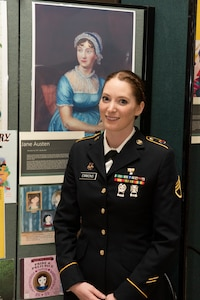 Army Staff Sgt. Trisha Emmons poses for a photo near a display of Jane Austen in the Green Mountain Armory on Camp Johnson, Vermont, March 18, 2021. Emmons, a human resources NCO with the Vermont Army National Guard's Medical Readiness Detachment, Garrison Support Command, was one of several Guardswomen who facilitated an online book reading and showcase of Guard uniforms and equipment for children at a local day care center. (U.S. Army National Guard photo by Don Branum)