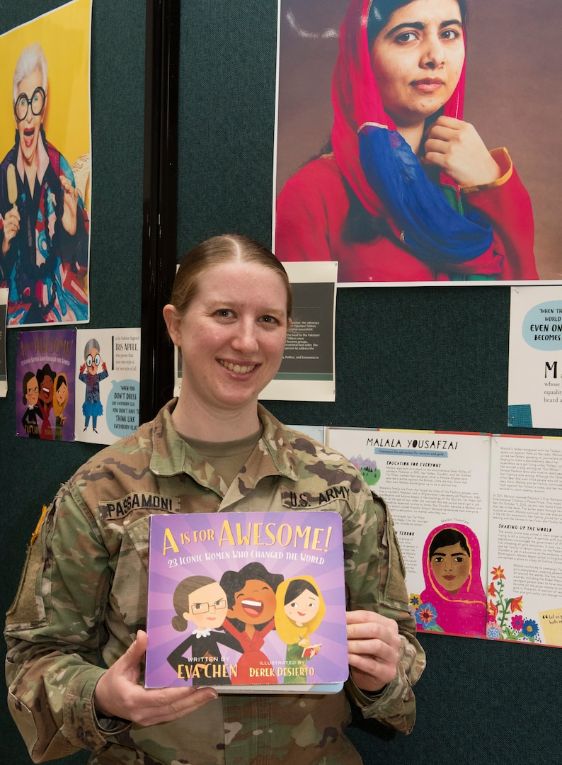 Chief Warrant Officer 2 Megan Passamoni poses in front of a display of Malala Yousafzai in the Green Mountain Armory at Camp Johnson, Vermont, March 18, 2021. Passamoni, a human resources technician with the Vermont Army National Guard's Headquarters Company, 86th Infantry Brigade Combat Team (Mountain), was one of several Guardswomen who facilitated a book reading and display of Guard uniforms and equipment for a local day care center. (U.S. Army National Guard photo by Don Branum)
