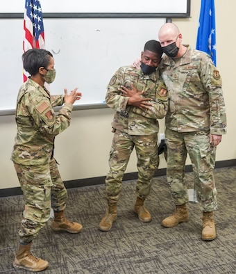 Chief Master Sgt. Christopher Walker, 75th Air Base Wing command chief, embraces Airman First Class Kamari Johnson, a defender with the 75th Security Forces Squadron, to congratulate Johnson's acceptance to the U.S. Air Force Academy Preparatory School while Col. Jenise Carroll, 75th Air Base Wing commander, looks on March 18, 2021, at Hill Air Force Base, Utah.