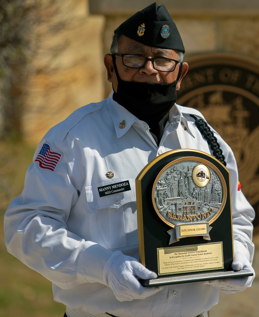 Manny Mendoza, Fort Sam Houston Memorial Services Detachment commander, poses with a commemorative plaque at the Fort Sam Houston National Cemetery in San Antonio March 15. The plaque was presented to commemorate the 40,000th funeral service conducted by the detachment.