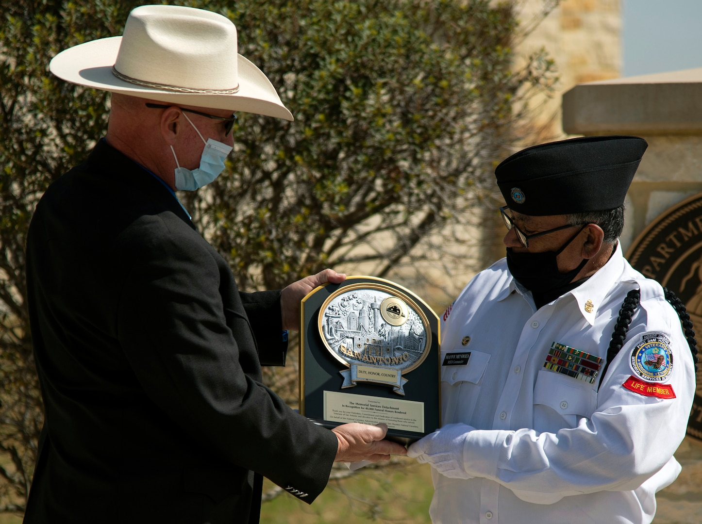 Robert C. (Bob) Winkler (left), assistant director of the U.S. Department of Veterans Affairs National Cemetery Administration Fort Sam Houston National Cemetery, presents a plaque to Manny Mendoza, Fort Sam Houston Memorial Services Detachment commander, at the Fort Sam Houston National Cemetery March 15. The plaque was given to the detachment to commemorate their 40,000th funeral service.