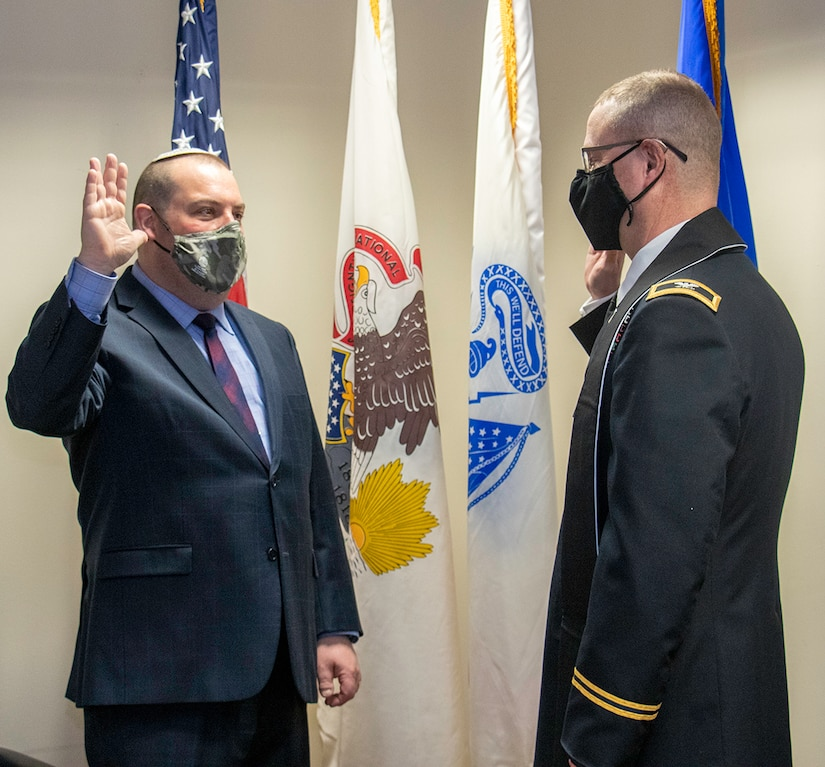 Rabbi Aaron Melman, of Northbrook, Illinois, recites the oath of commissioning as a captain in the Illinois Army National Guard administered by Chaplain (Col.) Stephen Foster, of Riverton, Illinois, Illinois National Guard State Chaplain, during a ceremony March 17 at Camp Lincoln, Springfield, Illinois.