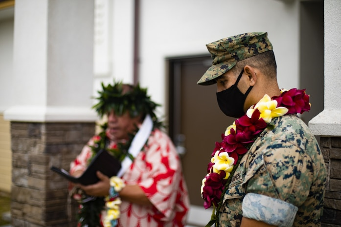 U.S. Marine Corps Col. Speros Koumparakis, commanding officer, Marine Corps Base Hawaii, listens as a prayer is read to bless the newly completed Fairway Inn, MCBH, March 15, 2021. It is Hawaiian tradition to conduct both a blessing and an untying of a Maile Lei at the grand opening to introduce the building to the community and protect it. (U.S. Marine Corps photo by Lance Cpl. Brandon Aultman)