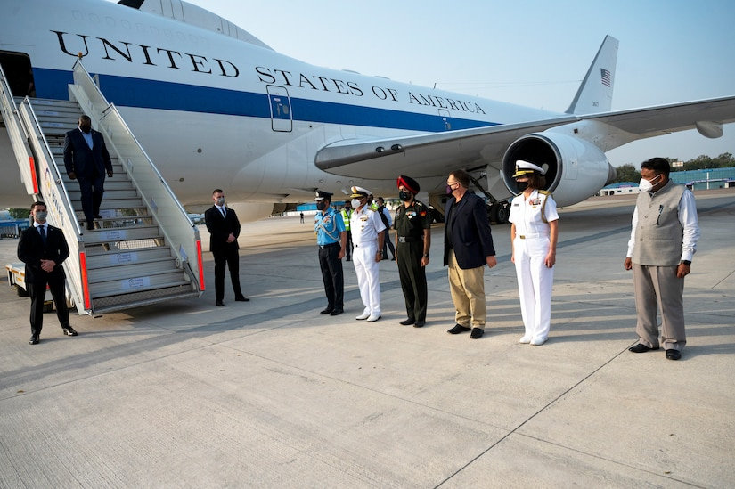 A man in business attire disembarks from an airplane bearing the words United States of America while six people stand in a line on the tarmac.