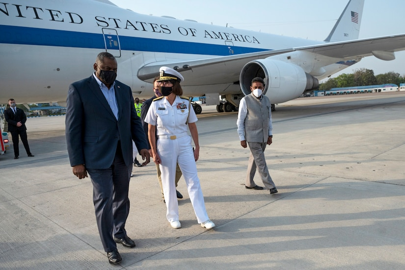 A man in business attire walks along the tarmac with a woman in a military uniform; a large plane bearing the words United States of America is in the background.