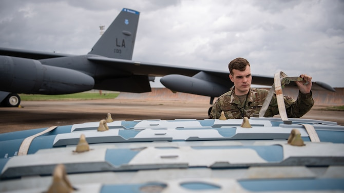 Airman 1st Class Aaron J. Vind, 2nd Aircraft Maintenance Squadron weapons load crew member, unties munitions from a trailer during Combat Hammer at Barksdale Air Force Base, La., Mar. 10, 2021. Combat Hammer was a week-long evaluation of the wing's capacity to generate, load and employ conventional weapons on target. (U.S. Air Force photo by Airman 1st Class Jacob B. Wrightsman)