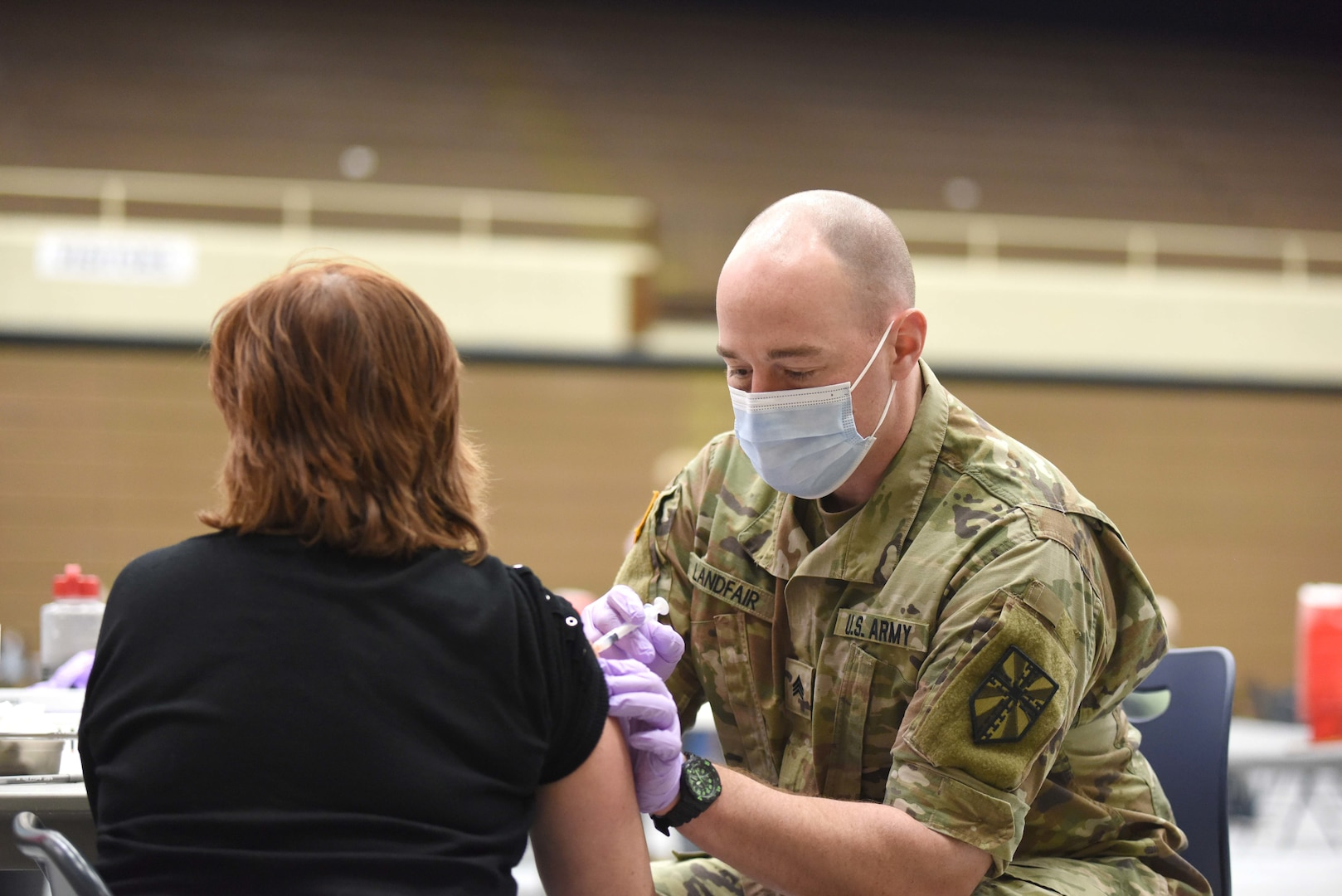 Army combat medic administers a coronavirus vaccine.