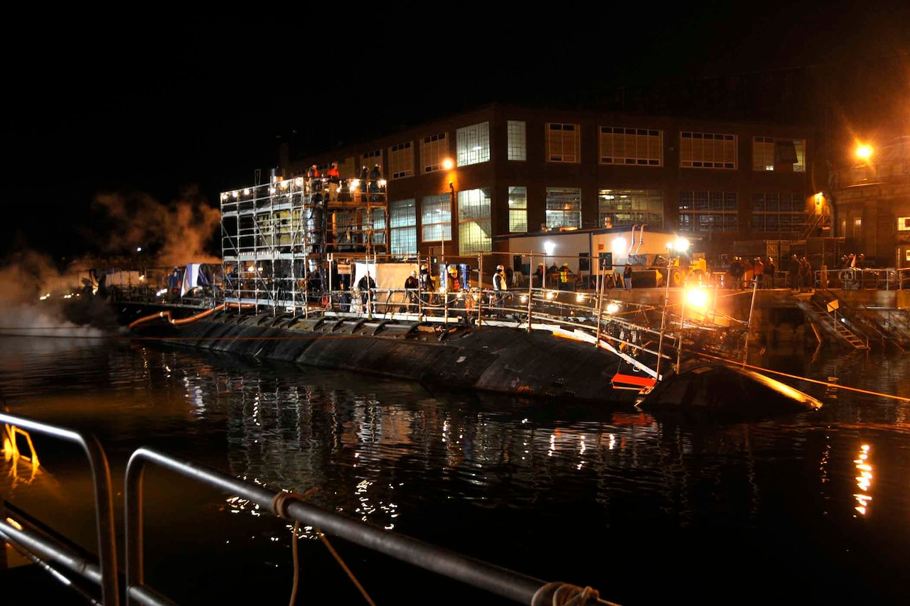 At night, a submarine sits submerged in the water in front of an industrial complex.