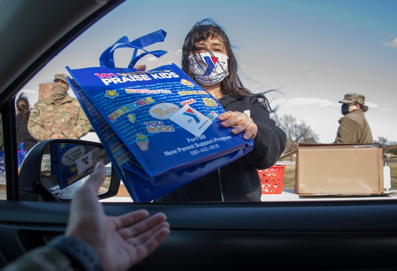 A member of the Armed Services YMCA (ASYMCA) of Altus Air Force Base (AFB) hands a welcome bag to an Airman during the ASYMCA open house drive-thru eventat Altus AFB, Oklahoma, March 18, 2021. The ASYMCA also handed out brochures that included information about various programs for Airmen and their families, including Operation Bring Baby Home, Hero's Pantry, Airmen Against Drunk Driving,the Volunteer Program and more. (U.S. Air Force photo by Airman 1st Class AmandaLovelace)
