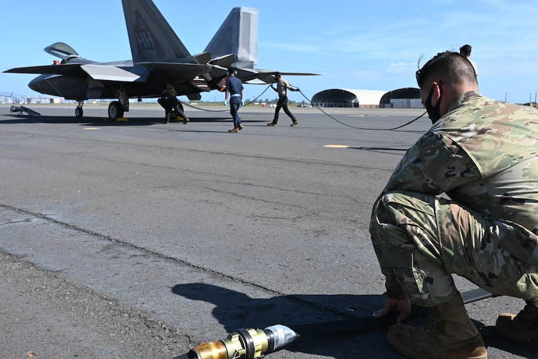 Tech Sgt. Robert Rabacal, 154th Aircraft Maintenance Squadron F-22 maintenance technician holds down a refueling hose while fellow Airmen position it towards an F-22 Raptor, Feb. 25, 2021, Joint Base Pearl Harbor-Hickam.