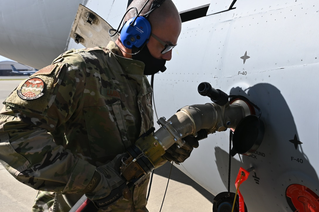 Senior Airman Samuel Lugo, 15th Aircraft Maintenance Squadron C-17 crew chief, attaches a refueling hose to a C-17 Globemaster III , Feb. 25, 2021, Joint Base Pearl Harbor-Hickam.