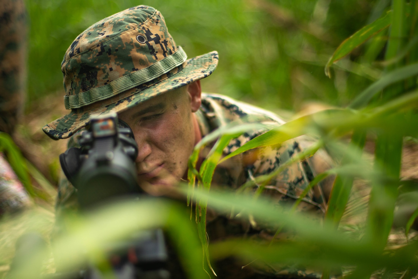 U.S. Marine Corps Lance Cpl. Clayton Takacs, a combat engineer with 3d Battalion, 8th Marine Regiment, 3d Marine Division, examines his sector of fire during Castaway 21.1 at Ie Shima, Okinawa, Japan, March 12, 2021. The exercise demonstrated the Marine Corps' ability to integrate with the joint force to seize and defend key maritime terrain, provide low-signature sustainment, and execute long-range precision fires in support of naval operations from an expeditionary advanced base. Takacs is a native of Orwell, Ohio.