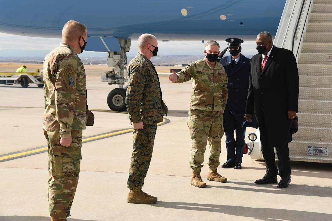 Three service members stand in a row to greet the Secretary of Defense, who has disembarked from a plane.