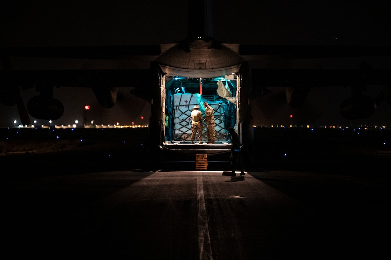 Airmen unload COVID-19 vaccines from a C-130 Hercules