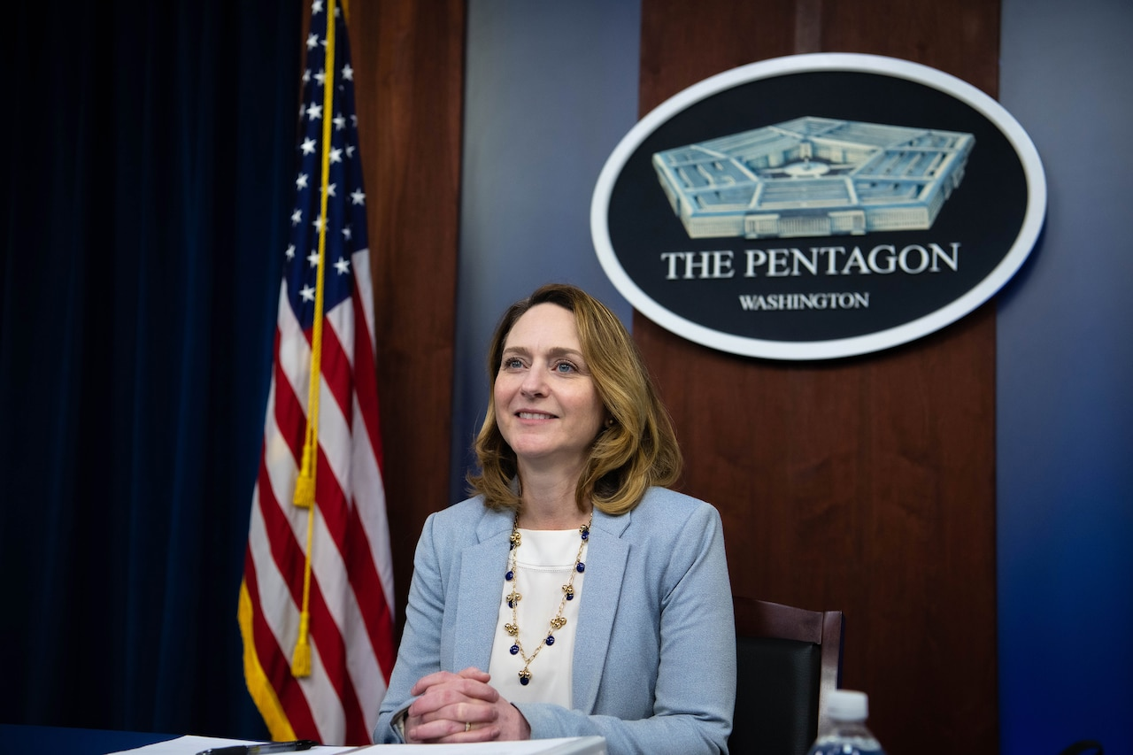 Deputy Defense Secretary Kathleen H. Hicks sits at a table, with a Pentagon seal displayed on the wall behind her.