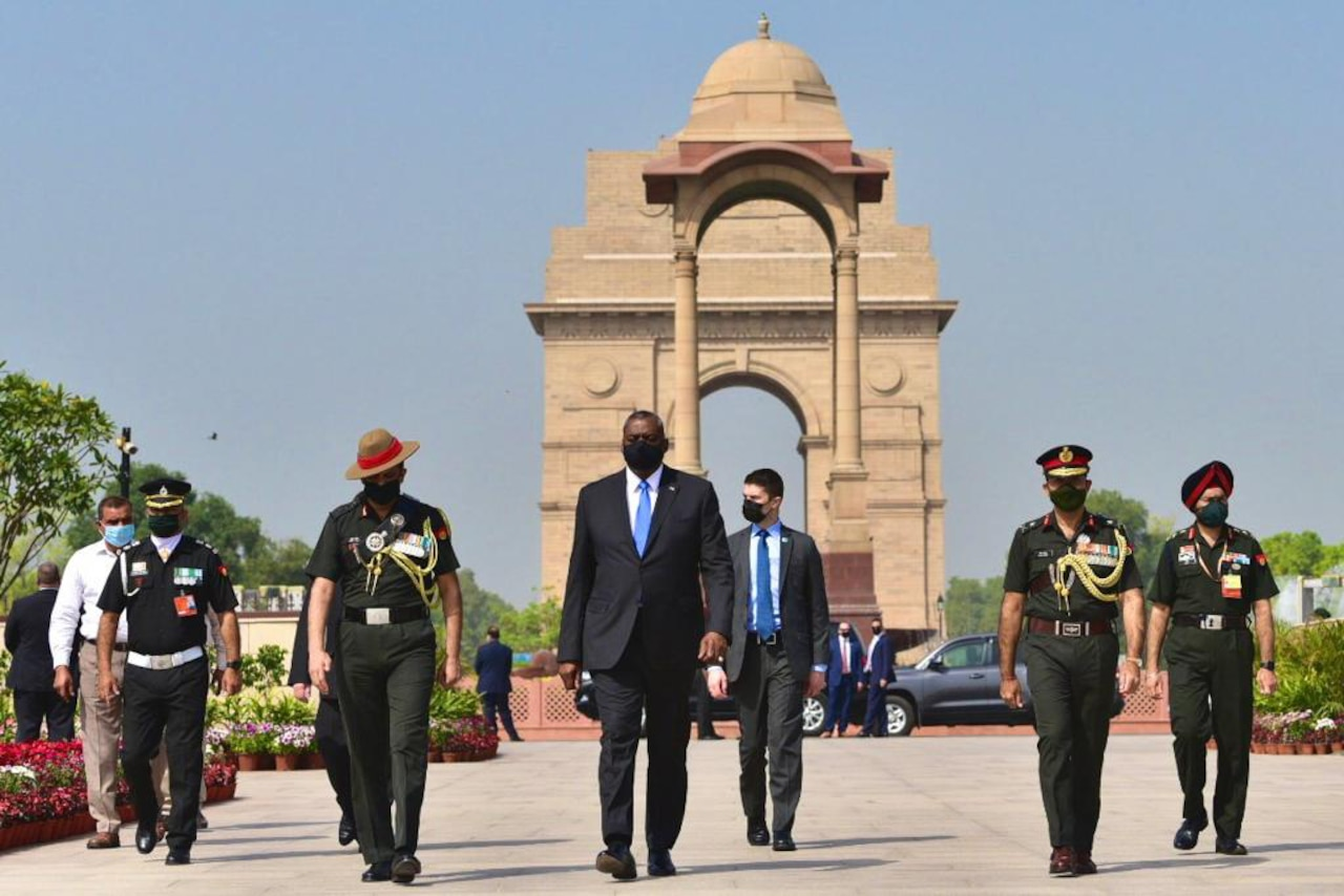 A group of men, some in military uniforms, walk toward the camera. The India Gate is behind them.