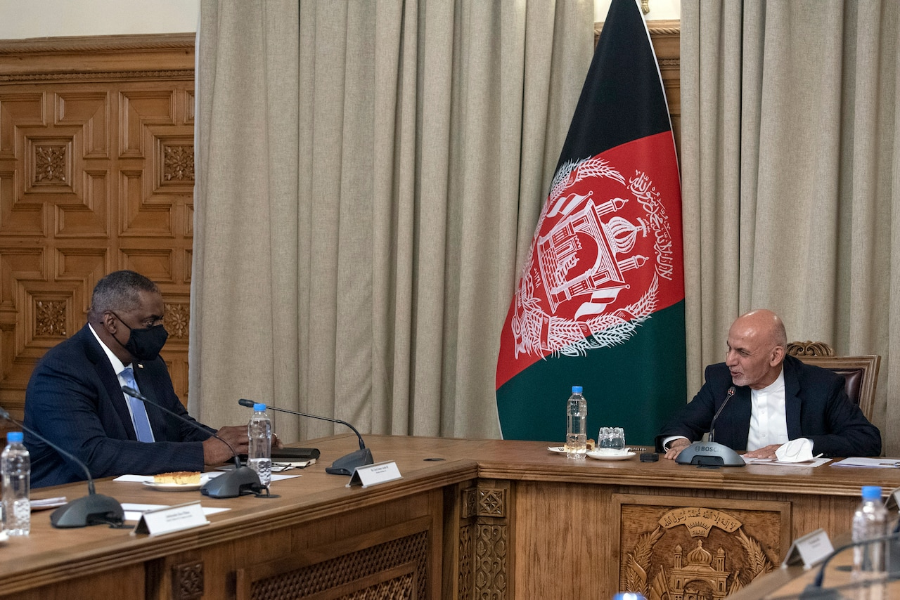 Secretary of Defense Lloyd J. Austin III talks with another civilian at a table in front of an Afghan flag.