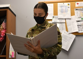 Senior Airman Weronika Baczek, a public health technician with the 104th Medical Group, views a binder, in her office at Barnes Air National Guard Base, Massachusetts, Feb. 17, 2021. Contact tracing is critical for safeguarding 104th Fighter Wing mission readiness and the health of our Barnestormers and surrounding communities from COVID-19. (U.S. Air National Guard courtesy photo)