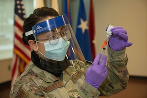 Master Sgt. Chelsea LaViolette, training and education NCOIC for the 102nd Medical Group, Otis Air Force Base, Mass., and an immunization technician for CBRNE Task Force, loads one dose of the new COVID-19 vaccine to inoculate one of the volunteers who will receive it, here, Jan. 4, 2021. The vaccine is currently available to select Soldiers and Airmen based off of risk and mission requirements, but will be available widely as supplies increase. (Massachusetts National Guard Photo by Sgt. Tricia Andriski)