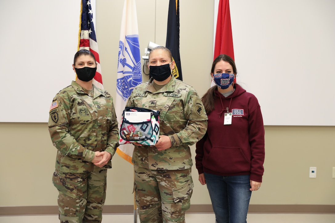 Ms. (Sgt. 1st Class) Kristen Bell, and Sgt. Teresa Gonzalez, 1st Civil Affairs and Psychological Operations Training Brigade, pose with Shelby Rangel, Center Director for the Ft. Bragg USO, following a presentation honoring Gonzalez as one of thirty female servicemembers across Ft. Bragg selected to be recognized during Women's History month.