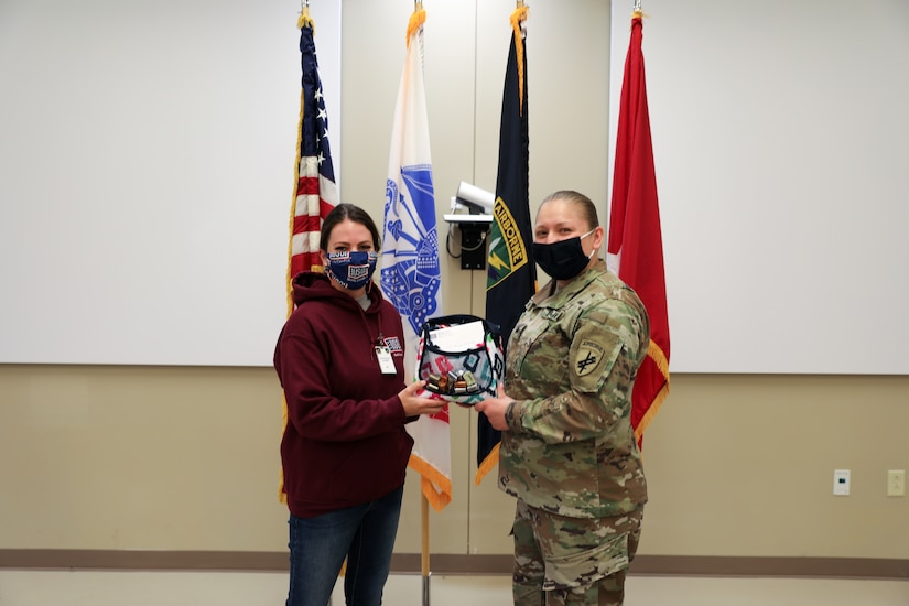 Shelby Rangel, Center Director for the Ft. Bragg USO, presents Sgt. Teresa Gonzalez, S1 NCOIC for the 1st Civil Affairs and Psychological Operations Training Brigade, with a USO sponsored gift bag. Gonzalez was nominated by her coworker, Ms. Kristen Bell, and recognized by the USO as one of thirty female servicemembers across Ft. Bragg to be honored during Women's History month.
