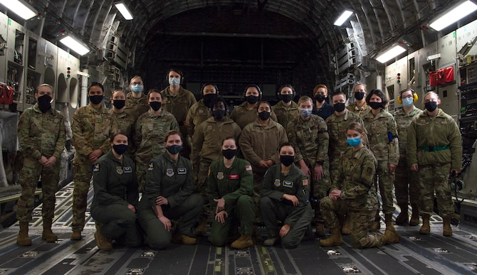 Team McChord Airmen pose for a group photo inside a C-17 Globemaster III at Joint Base Lewis-McChord, Washington, Dec. 14, 2020. The all-female crew prepared, launched and executed a flight-training mission in honor of women in the military. (U.S. Air Force photo by Senior Airman Tryphena Mayhugh)