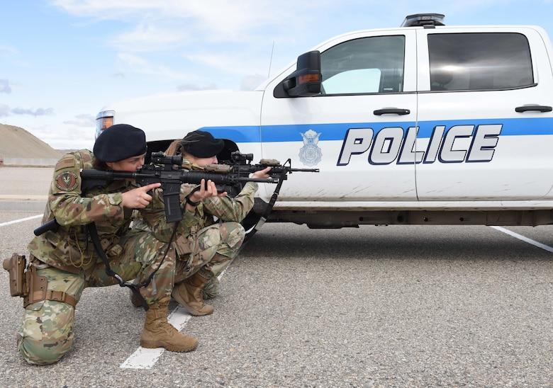 Two female Security Forces Airmen pose with their weapons in front of a police truck.