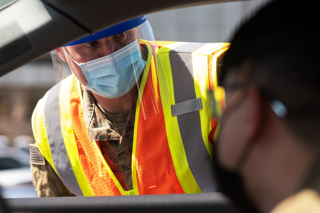 A soldier wearing a face mask leans over into a car window to answer a question.
