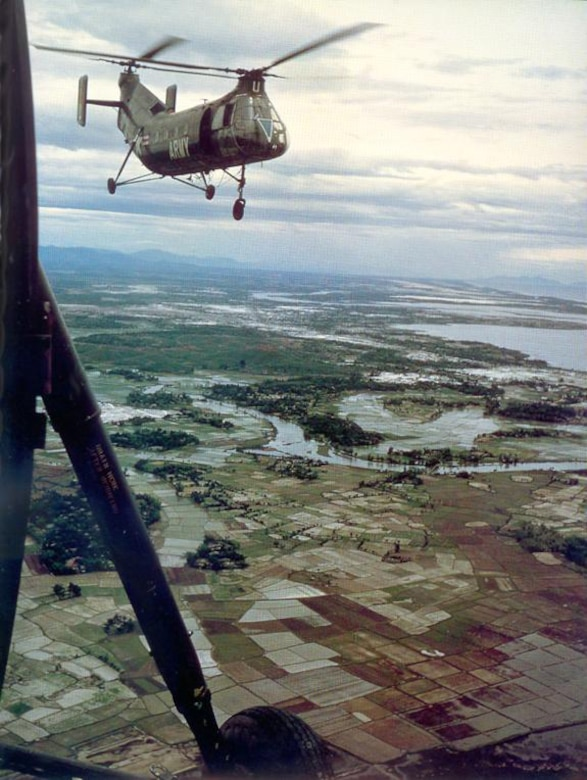 Helicopters fly above fields and bodies of water.