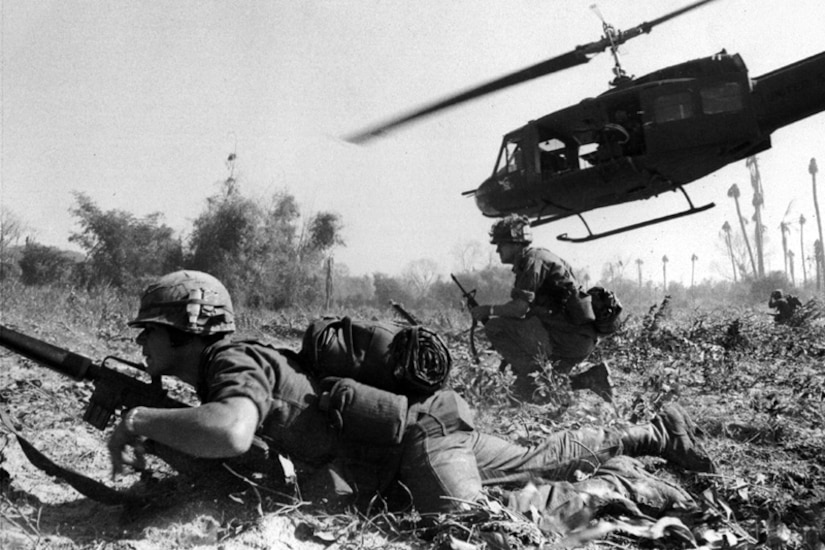 A helicopter flies close to ground troops in a field.