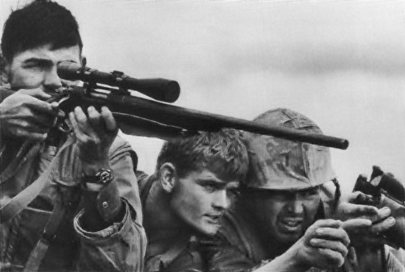 A sniper aims a rifle while two soldiers discuss a target.