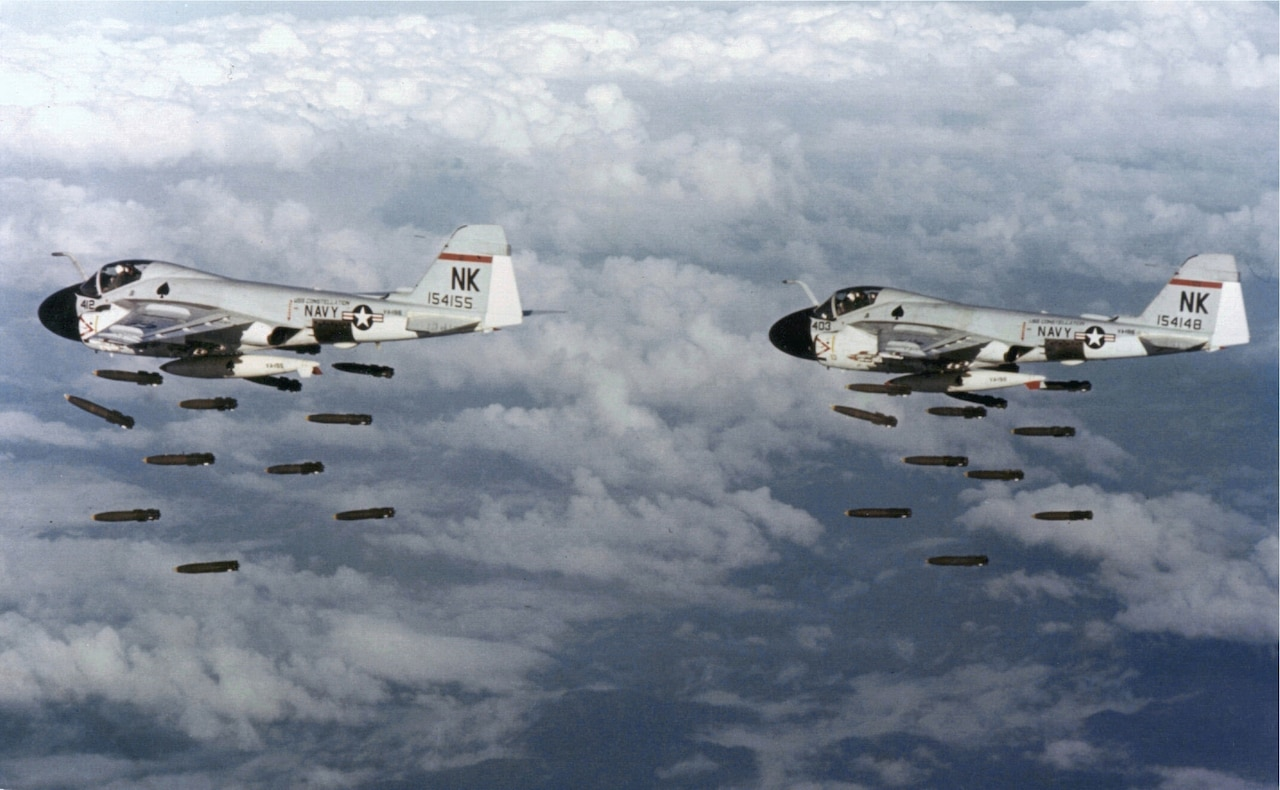 American aircraft drop bombs from above the clouds.