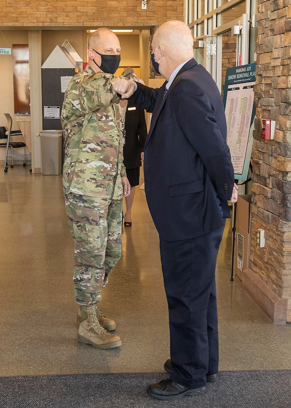 NRO Deputy Director Maj. Gen. Michael Guetlein elbow bumps Acting Secretary of the Air Force John Roth upon his arrival to Aerospace Data Facility Colorado March 11, 2021. During his visit, Roth got a firsthand look at how NRO operations stay mission-ready through the capabilities of airmen and assets at the ADF-C. He spoke with airmen, soldiers, and sailors on the operations watch floor for a broader understanding of the collaboration required to provide data to defense, intelligence, and civil agencies supporting the U.S. Government and its allies.
