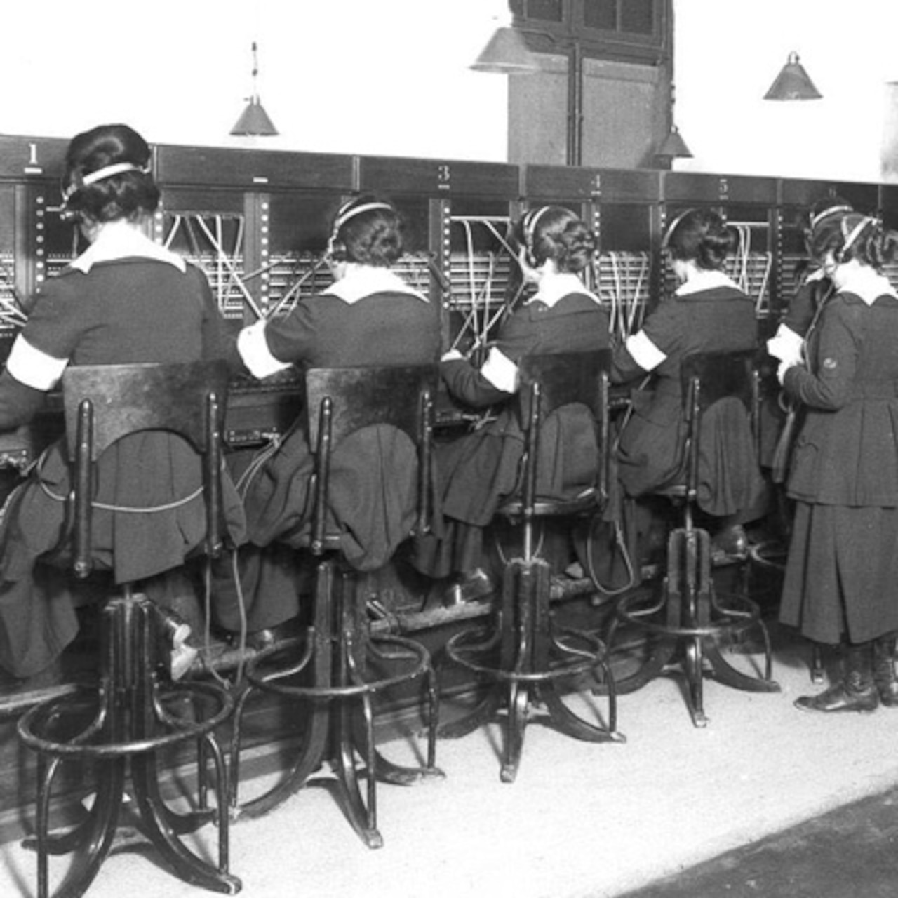Women sit in a row and work at a telephone switchboard.