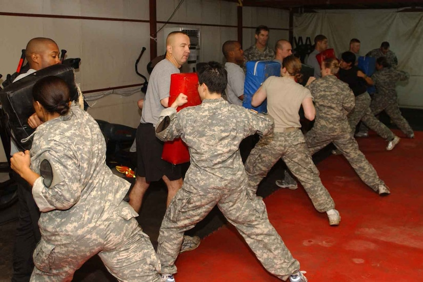 Female soldiers hit pads in a self-defense class.