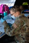 Senior Airman Erin Linhares, an aerospace medic with the 157th Medical Group, draws a dose of COVID-19 vaccine March 12, 2021, at the Exeter vaccination site.