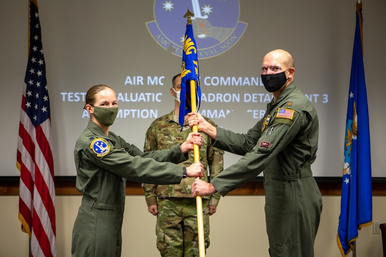 Major Jacob C. Johnson, the new commander of Detachment 3 Air Mobility Command Test and Evaluation Squadron, receives the unit guidon from Lt. Col. Maryann Karlen, AMC TES commander, during an Assumption of Command ceremony March 15, at Edwards Air Force Base, California. (Air Force photo by Senior Master Sgt. Alexander Berry)