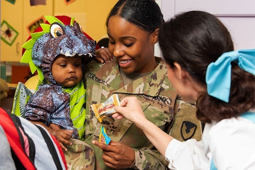 A soldier holding a child receives a snack from another person.