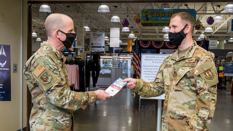 Brig. Gen. Matthew Higer, 412th Test Wing Commander, hands an Air Force Assistance Fund pamphlet to Maj. Peter Zevetchin, Air Force Materiel Command, at Edwards Air Force Base, California, March 22. (Air Force photo by Giancarlo Casem)