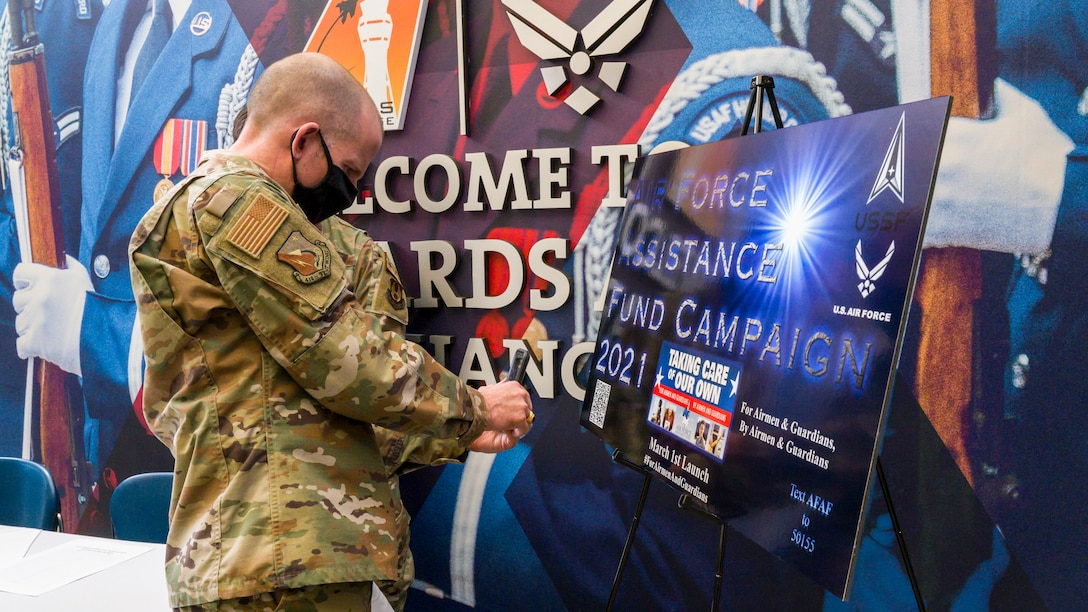 """Brig. Gen. Matthew Higer, 412th Test Wing Commander, scans the QR code for the Air Force Assistance Fund on his cell phone at Edwards Air Force Base, California, March 22. The campaign, titled """"For Airmen & Guardians, By Airmen & Guardians,"""" runs until April 30. (Air Force photo by Giancarlo Casem)"""